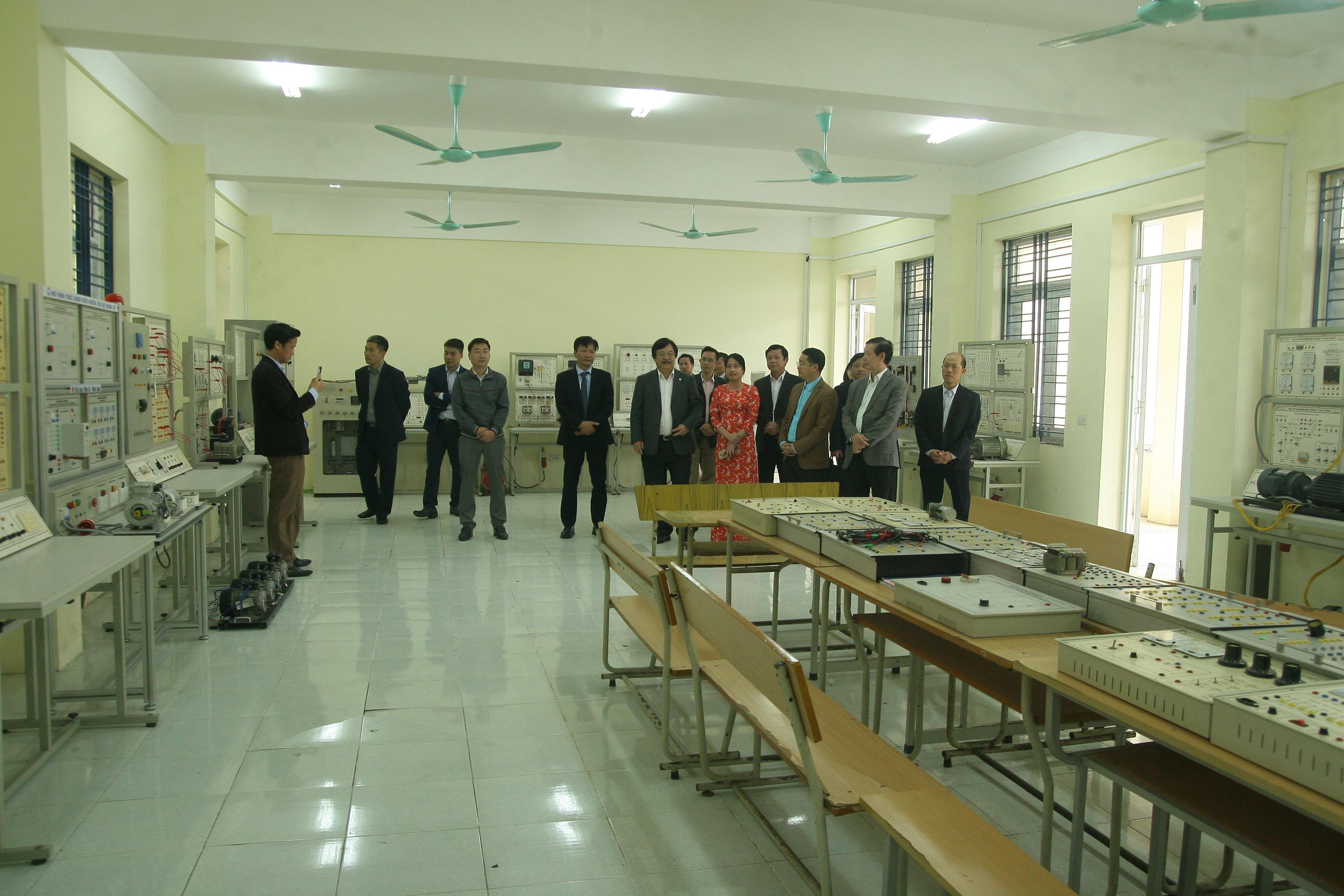 Đoàn công tác thăm quan một phòng thực hành khoa Điện của nhà trường.